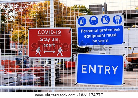 Entrance to a construction site with warning signs attached to a fence. Covid 19 stay 2 metres apart. Personal protective equipment must be worn. Entry. Zdjęcia stock ©