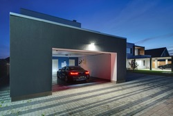 Entrance to a garage with the shining lamps in the modern country house. In the garage there is a black car with glowing parking lights. Around the house there is a tiled area. Horizontal.