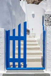 Entrance to a traditional Greek island styled home with a blue gate and whitewashed steps and walls. Taken on the island of Santorini, Greece. Vertical orientation.