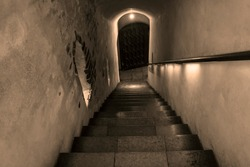Entrance to an a underground. Cellar Stairs leading down to stone and brick lower level in black and white