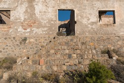 Entrance to an old house in a mining complex in southern Spain, there is a stone staircase, there is a door and 2 windows