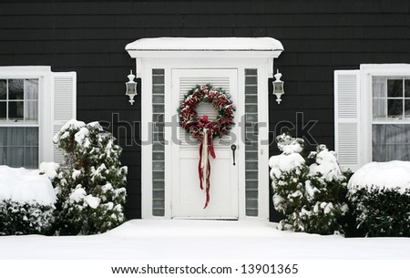 entrance to home with holiday wreath and snow