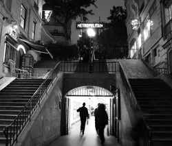 Entrance to the metro station Lamarck caulaincourt in Paris (18th arrondissement) night view in black and white. Art deco architecture. several people walk and enter the subway.