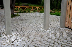 entrance to the park delimited by a passage between concrete columns which prevents cars from entering the park and the cobblestone pond granite cube path