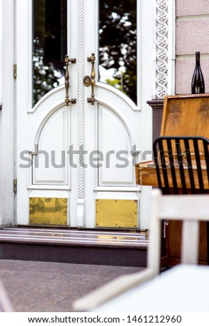 entrance with a stone threshold at the white closed door with a glass insert and iron handles in the restaurant with a piano near the facade of the building. #1461212960