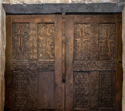 Entrance with aged sacred symbols, religious decoration in the church of the Nativity in Bethlehem, Palestine. Medieval wooden door with carved Christian crosses and ancient inscriptions on the gate.