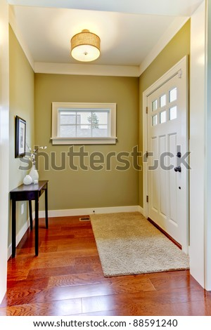 Entrance with green walls and cherry hardwood floor.