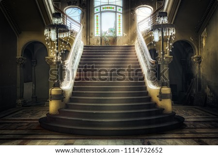 Entrance with symmetrical stairs of an abandoned casino. Sunlight shines through the windows and lights the darkness. - Shutterstock ID 1114732652