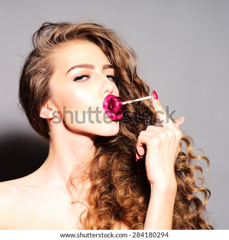 Entrancing playful young undressed woman with curly hair and bright pink lips holding with finger purple round lollipop in mouth looking forward standing on grey background, square picture