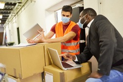 Entrepreneur and warehouse clerk check packages with computer for online shipping