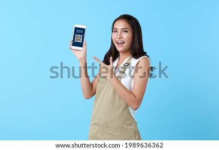 Entrepreneur asian woman showing smartphone scan QR code for payment on blue background.