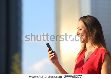 Entrepreneur business woman using a smart phone with office buildings in the background stock photo