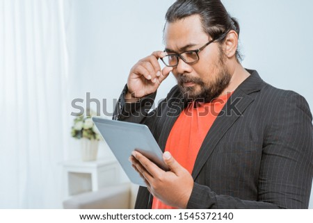 entrepreneur concentrating while reading his tablet pc. serious businessman with tab