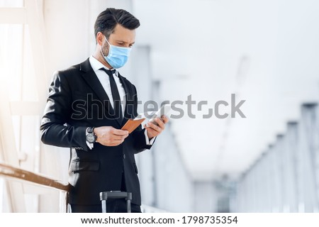 Entrepreneur in face mask using phone while waiting for flight in airport, holding passport and flight tickets, copy space