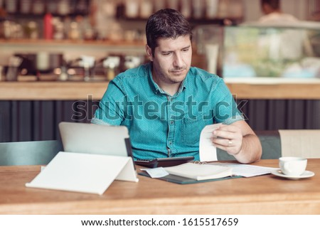 Entrepreneur managing his small business - Businessman looking overwhelmed - Young coffee shop owner going through paperwork