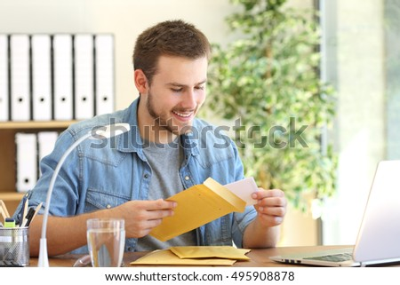 Entrepreneur opening a padded envelope in a desktop at office