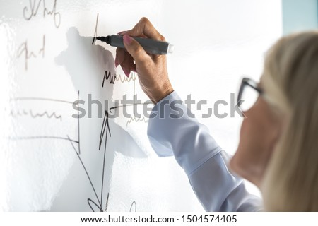 Entrepreneur 50s female writing business plan using flip chart in office close up focus on infographics handwritten information, coach perform presentation on white board concept of training seminar