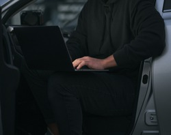 entrepreneur using laptop in car. low key photo without a face