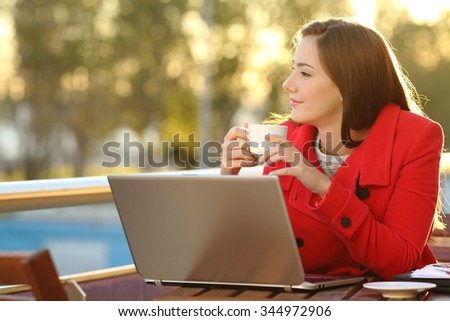 Entrepreneur with a laptop relaxing in a coffee shop and looking forward