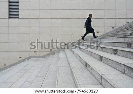 Entrepreneur with briefcase running up the stairs as he is late #794560129