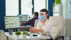 Entrepreneur with protection mask and visor applying sanitizer gel rubbing hands before typing at computer. Businesswoman in new normal workplace disinfecting while colleagues working in background