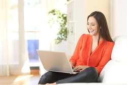 Entrepreneur woman wearing orange blouse working with a laptop sitting on a couch at home