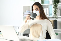 Entrepreneur woman wearing protective mask with spilled coffee over shirt at the office