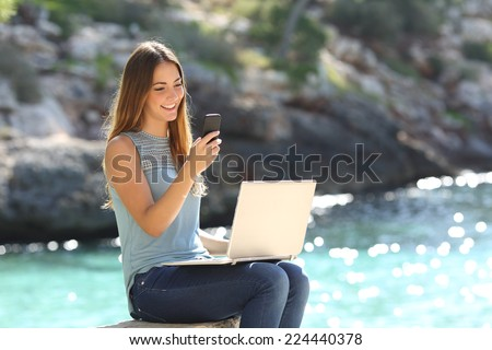 Entrepreneur woman working with a phone and a laptop on holidays in a tropical beach