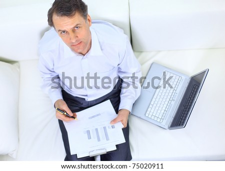 entrepreneur working from home looking very relaxed in his sofa browsing the web in his laptop computer