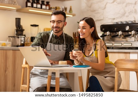 Entrepreneurs drinking coffee. Couple of successful young entrepreneurs drinking coffee and watching video on laptop