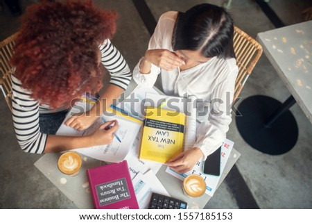 Entrepreneurs studying. Top view of two entrepreneurs studying tax law after launching business