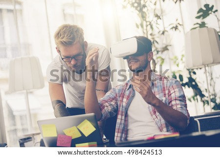 Entrepreneurs testing virtual reality technology with colleague in office.
