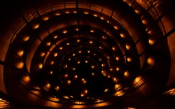 Entry to Ruakuri cave with spiral staircase, Waitomo, New Zealand. Spiral stairway with many lights in the dark. Abstract photography of underground tunnel urban architecture.
