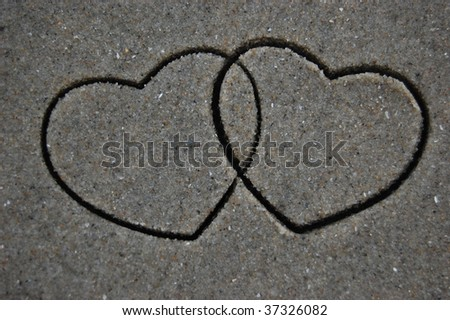 Entwined cookie cutter hearts impression in the sand