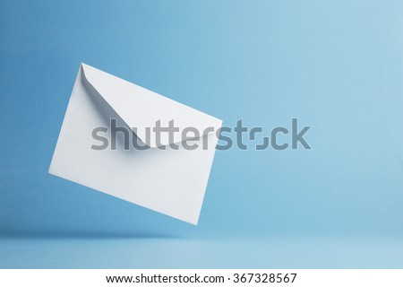 Envelope falling on the ground, blue background with negative space