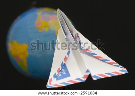 Envelope folded into an airplane with a blurred globe as background