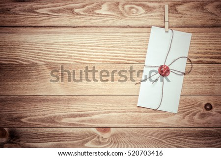 Envelope hanging on rope on wooden background #520703416