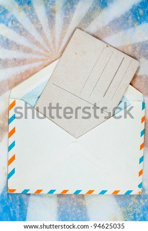Envelope of Air mail  and old postcard on a grunge retro sunburst background