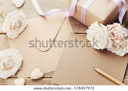 Envelope or letter, gift, paper card and vintage rose flowers on rustic wooden table for greeting on Mother or Woman Day