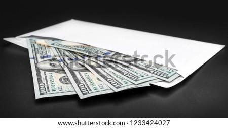 Envelope with dollar bills on black background. #1233424027