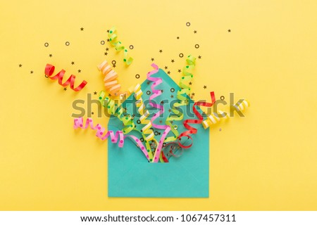 Envelope with party confetti explosion on yellow background. Invitation card, flat lay. - Shutterstock ID 1067457311