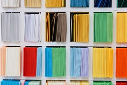 Envelopes stacks sorted on a shelf by color. Colorful mail wraps arranged in categories.