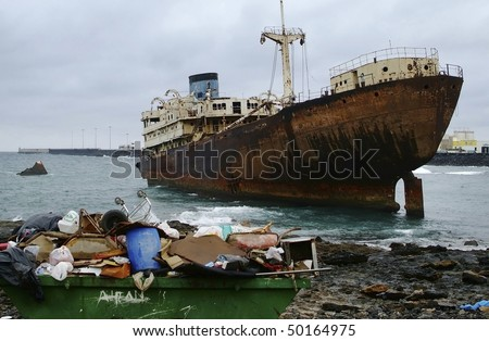 environment concept, garbage in container and abandoned rusty ship as background