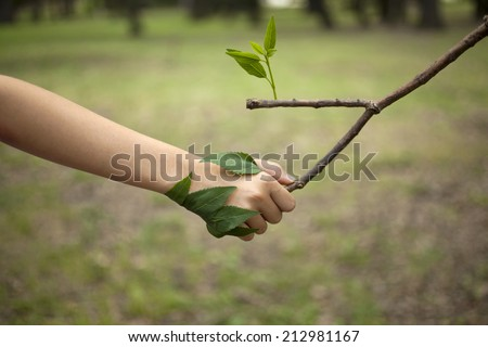 Environment concept. Handshake between human hand and tree.