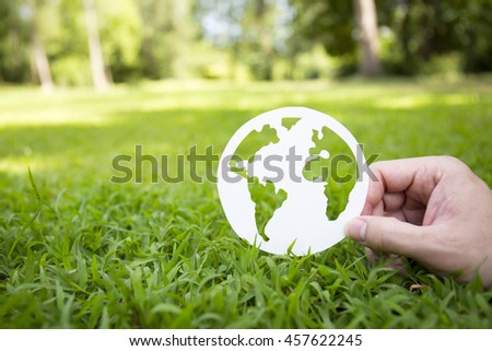 Environment concept, paper globe on the grass with hands, blur #457622245