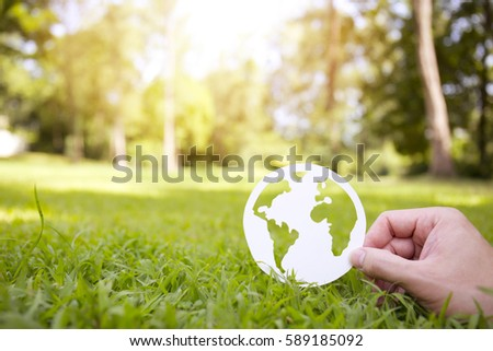 Environment concept, paper globe on the grass with hands, blur #589185092