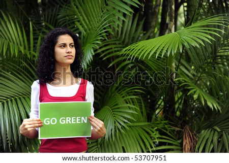 environment conservation: woman in the forest holding a go green  sign smiling