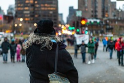 Environmental activists march in city. A bystander is seen from the back, wearing a black hat and jacket, woman stands alone in the city during a protest held by environmentalists, with copy-space