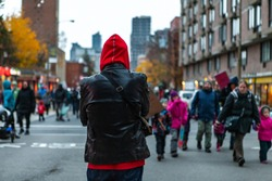 Environmental activists march in city. A bystander watches on as a large crowd of ecological protestors marches towards the camera, person wearing a hood from behind with blurred street in background