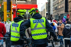 Environmental activists march in city. A rear view of two police cyclists standing by their patrol bikes and talking during a protest by eco-activists, a blurry street scene is seen in background.